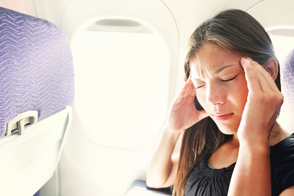 Fear of flying woman in plane airsick with stress headache
