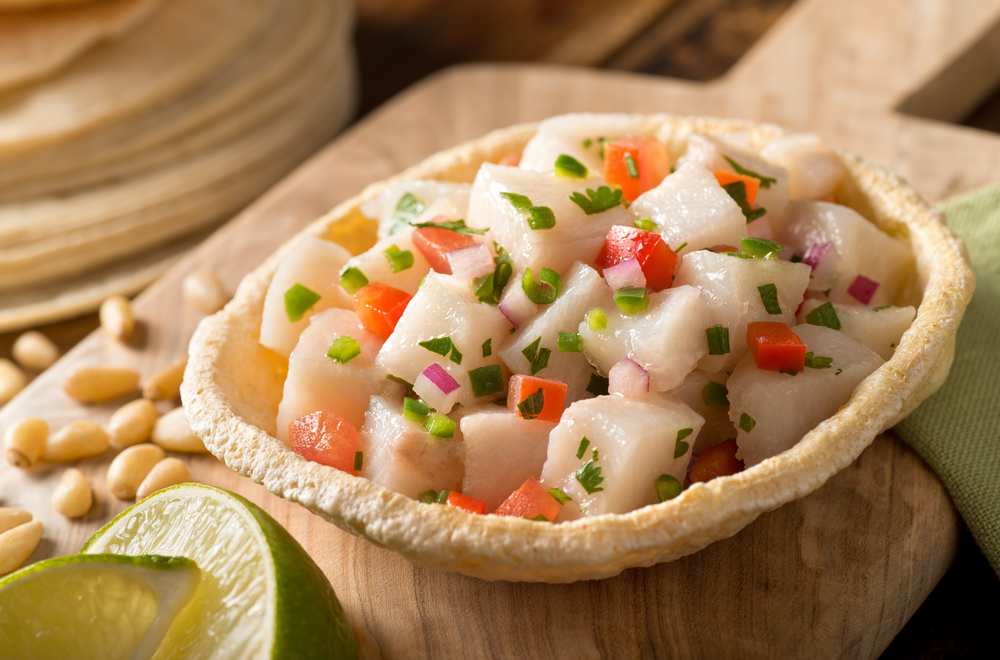 A freshly made white fish ceviche with tomato, red onion, cilantro, red pepper, lime, and serrano pepper.